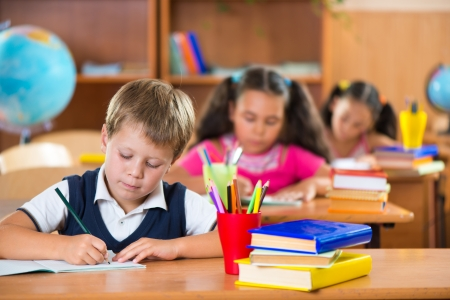 kid friendly: Cute schoolchildren during lesson in classroom at school Stock Photo