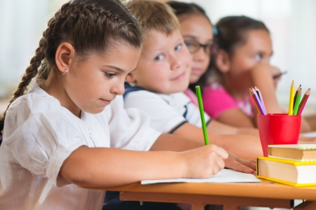 diligent: Four diligent pupils sitting in row and studying at classroom
