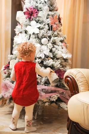 Cute little girl in red dress decorating christmas tree photo