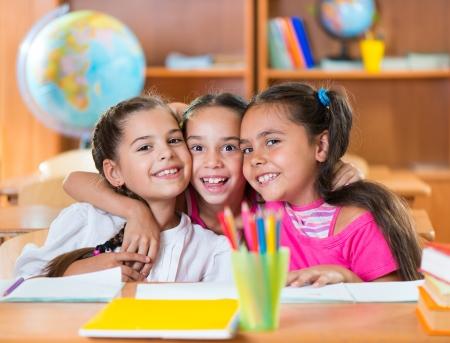 kid friendly: Portrait of smart schoolchildren looking at camera in classroom