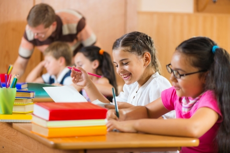 diligente: Retrato de alumno aplicado feliz mirando a su compa�ero de clase en la lecci�n