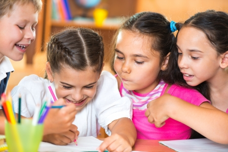 Group of cute schoolchildren drawing and having fun in classroom photo
