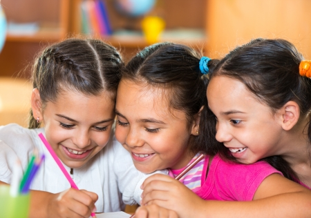 schoolchildren: Group of cute schoolchildren drawing and having fun in classroom