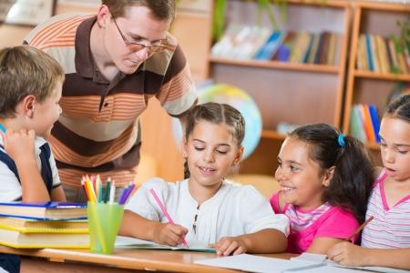 diligente: Retrato de colegiales diligentes y su profesor que habla en clase