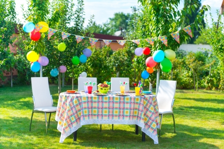 dinner party people: Prepared birthday table in summer green garden