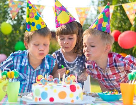 globos de cumplea�os: Ni�os celebrando la fiesta de cumplea�os y soplar las velas en la torta Foto de archivo