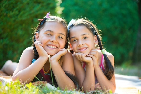 Image of two happy sisters having fun in the park photo
