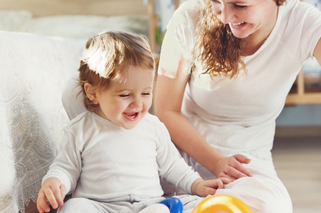 Young mother playing with her baby son at home Standard-Bild