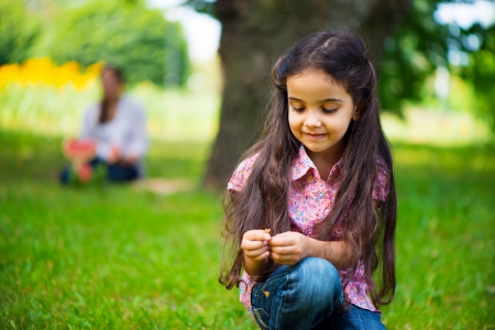 Cute hispanic girl take seat in park with mother on background