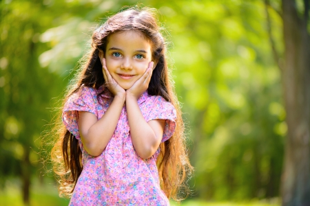 pretty young girl: Portrait of hispanic girl with deep blue eyes in sunny park