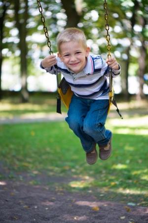 Cute little blond boy swinging on swings Stock Photo - 22280429