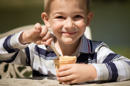 Smiling little boy eating ice-cream at table photo