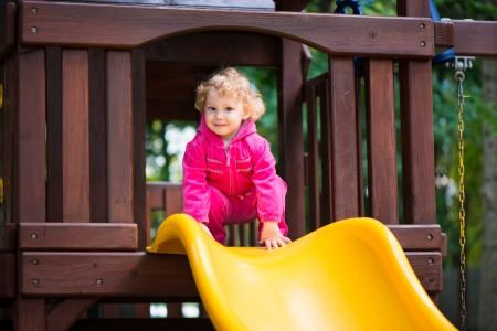 Curly haired blonde girl sliding at playground Stock Photo - 22280433