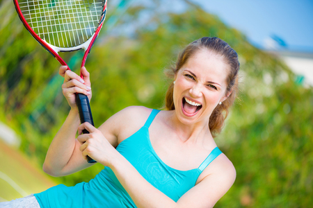Successful sportswoman with racket at the tennis court photo