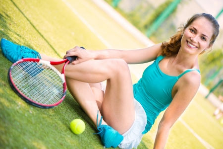 Young female tennis player resting on the tennis court after match photo