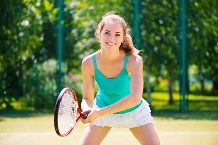 Portrait of a young tennis player standing ready for a serve  photo