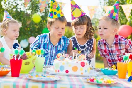 velitas de cumpleaños: Niños celebrando la fiesta de cumpleaños y soplar las velas en la torta Foto de archivo