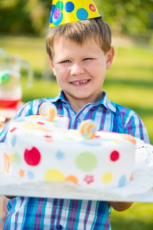 childs birthday party: Happy boy holding cake at childs birthday party