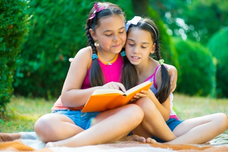Hispanic sisters reading book in summer park photo