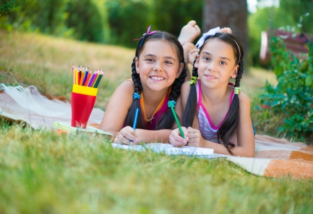 Happy hispanic sisters drawing in summer park photo