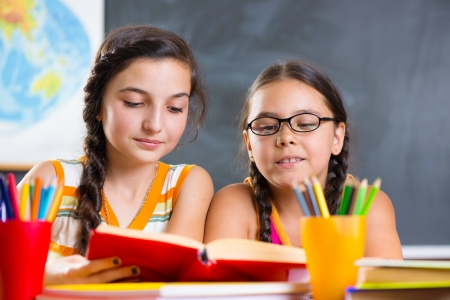 look latino: Portrait of two beautiful schoolgirl studying in classroom Stock Photo