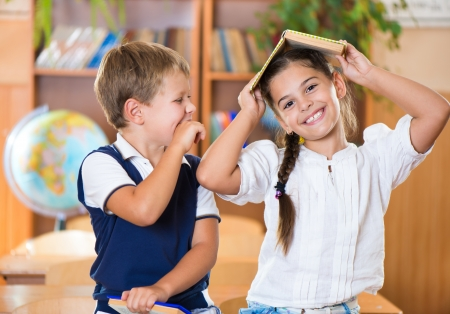 Two happy schoolchildren have fun in classroom at school  Stock Photo