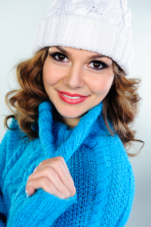 Portrait of beautiful young woman in blue knitted sweater and white hat photo