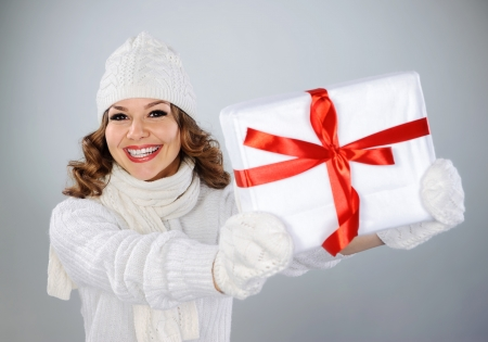 Beautiful young woman in white knitted hat holding Christmas present box with red ribbon photo