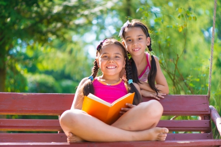 child studying: Happy hispanic sisters reading book in summer park Stock Photo