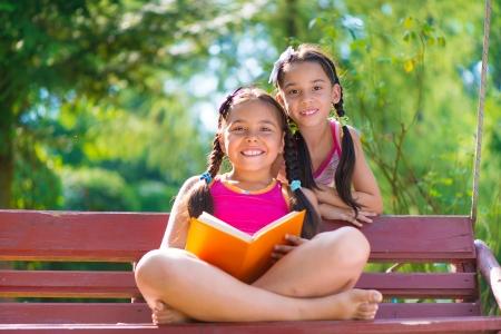 niños estudiando: Hermanas felices hispánica que lee el libro en parque del verano