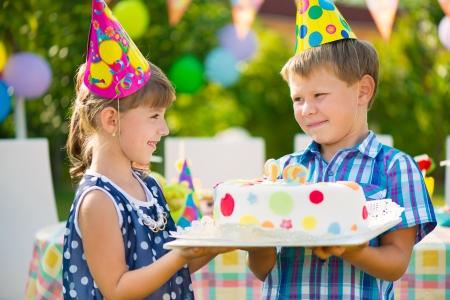 Cute children in love holding cake at birthday party Standard-Bild