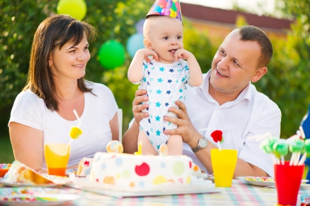 first day: Happy family celebrating first birthday of baby son Stock Photo