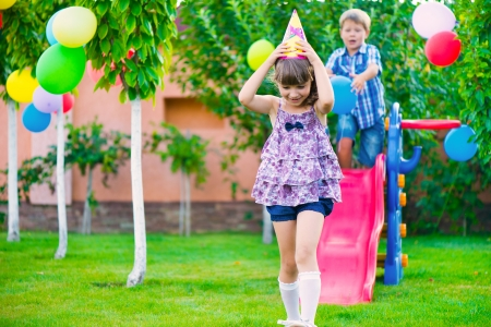 Two happy children sliding at playground during birthday party Stock Photo - 22814174