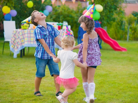 Three little kids celebrating birthday dancing roundelay photo