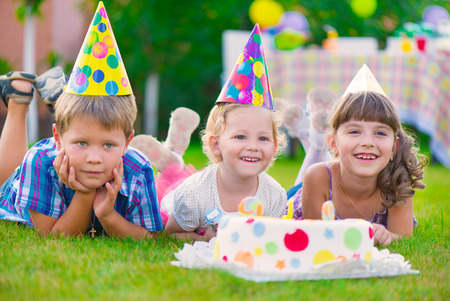 Three little kids celebrating birthday on green grass photo
