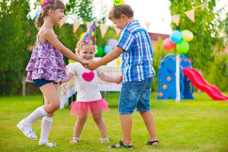 Three little kids celebrating birthday dancing roundelay Standard-Bild