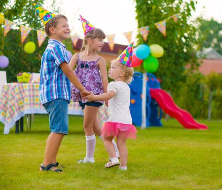 balloons party: Three little kids celebrating birthday dancing roundelay Stock Photo