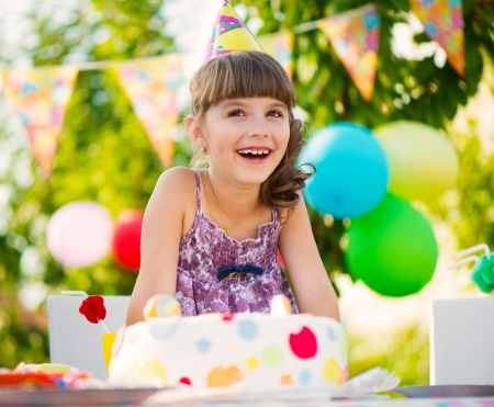 Happy pretty girl with cake at birthday party photo