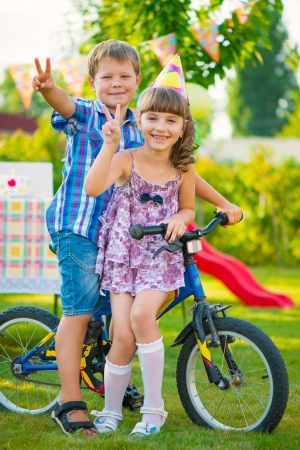 Two happy children in love sitting on bicycle Stock Photo