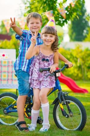 Two happy children in love sitting on bicycle Standard-Bild