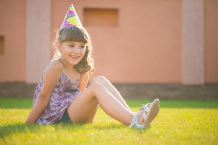 Happy pretty girl sitting on green grass in hat at birthday party photo
