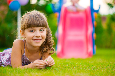 Pretty girl lying on green grass at playground photo