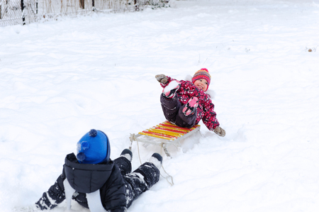 Cute kindergarten boy pulling his young sister on sled photo