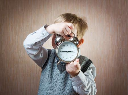 diligente: Retrato de ni�o lindo diligente con despertador