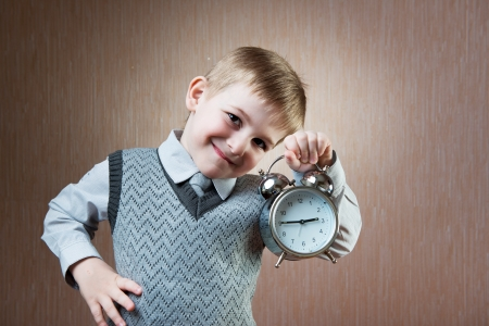 diligent: Portrait of cute diligent boy holding alarm clock