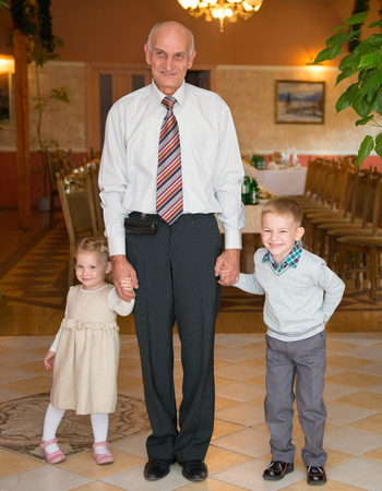 Happy grandfather with his grandchildren at restaurant before birthday party photo