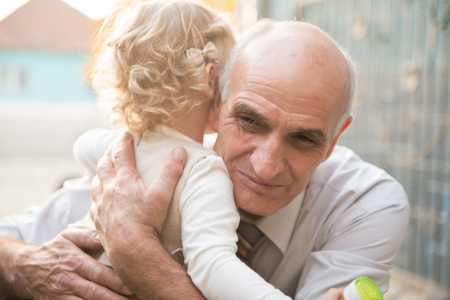 Happy grandfather with cute curly granddaughter Stock Photo