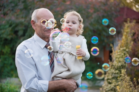 Happy grandfather and cute curly granddaughter blowing soap bubbles photo