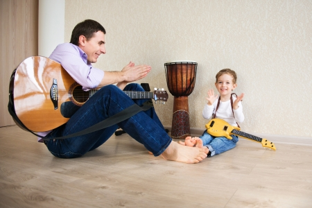 child singing: Young father with his little son playing guitar Stock Photo