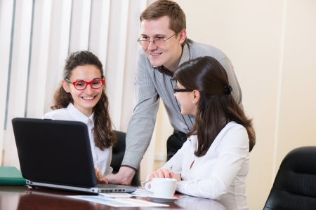 Happy young business people talking on meeting at office photo